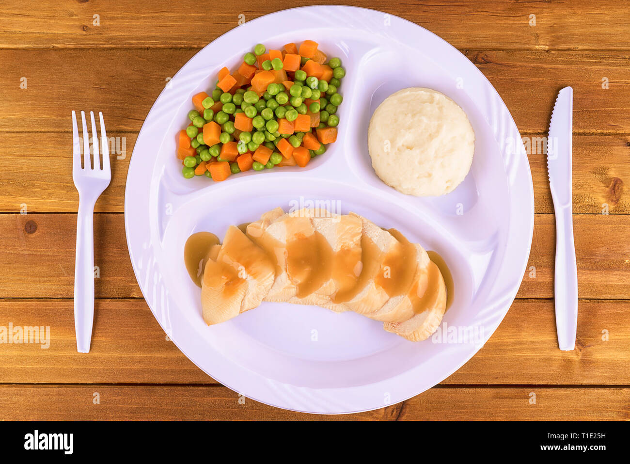 Sliced chicken tv dinner on wooden background, top view. - Stock Image