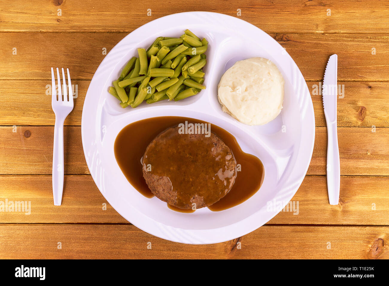 Beef patty tv dinner on wooden background, top view. - Stock Image