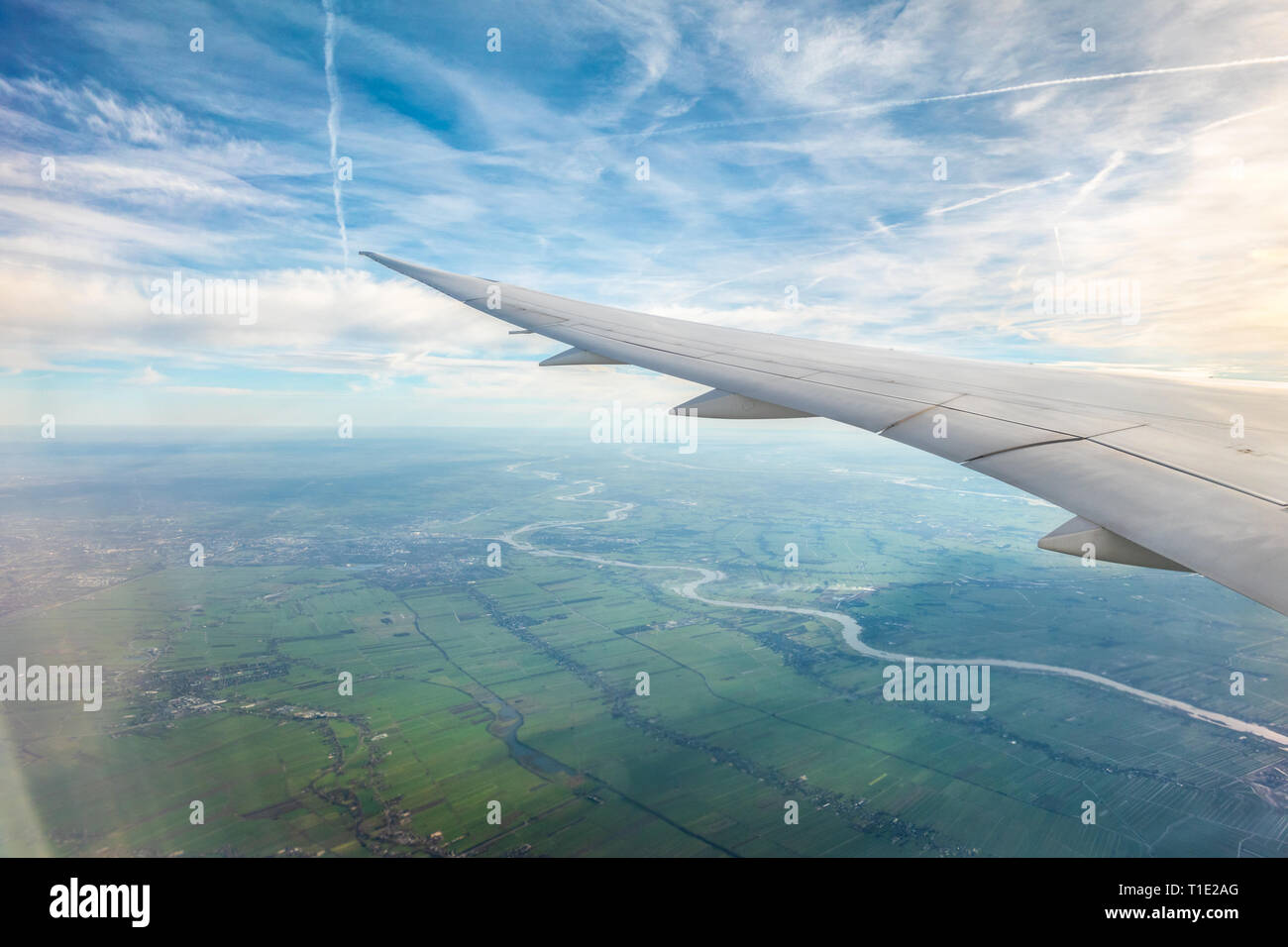 Jet airplane aeroplane plane trails contrails or Cirrus Aviaticus over Holland from the window of a Boeing 787 8 Dreamliner Stock Photo