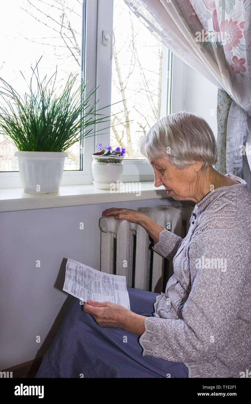 The senior woman holding gas bill in front of heating radiator. Payment for heating in winter. - Stock Image