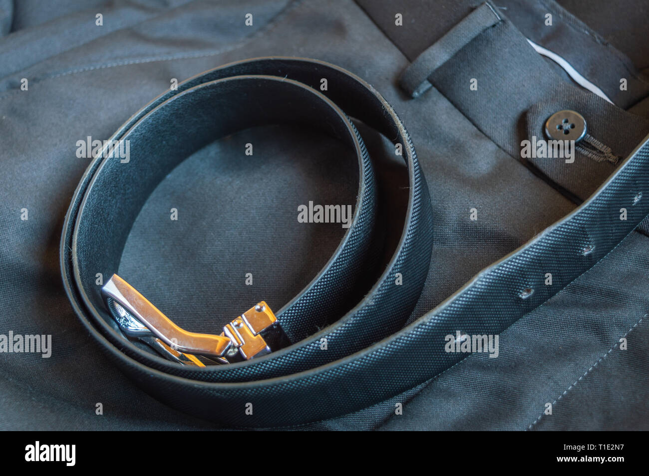 A black leather belt kept on a formal pant trouser Stock Photo