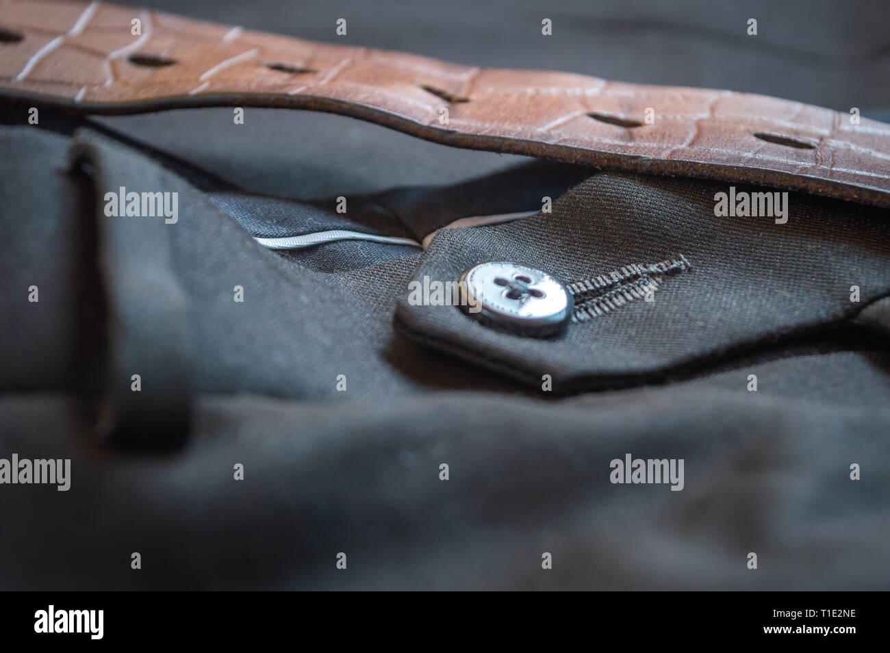 Close up of the button of a grey formal pant with a brown leather belt - Stock Image