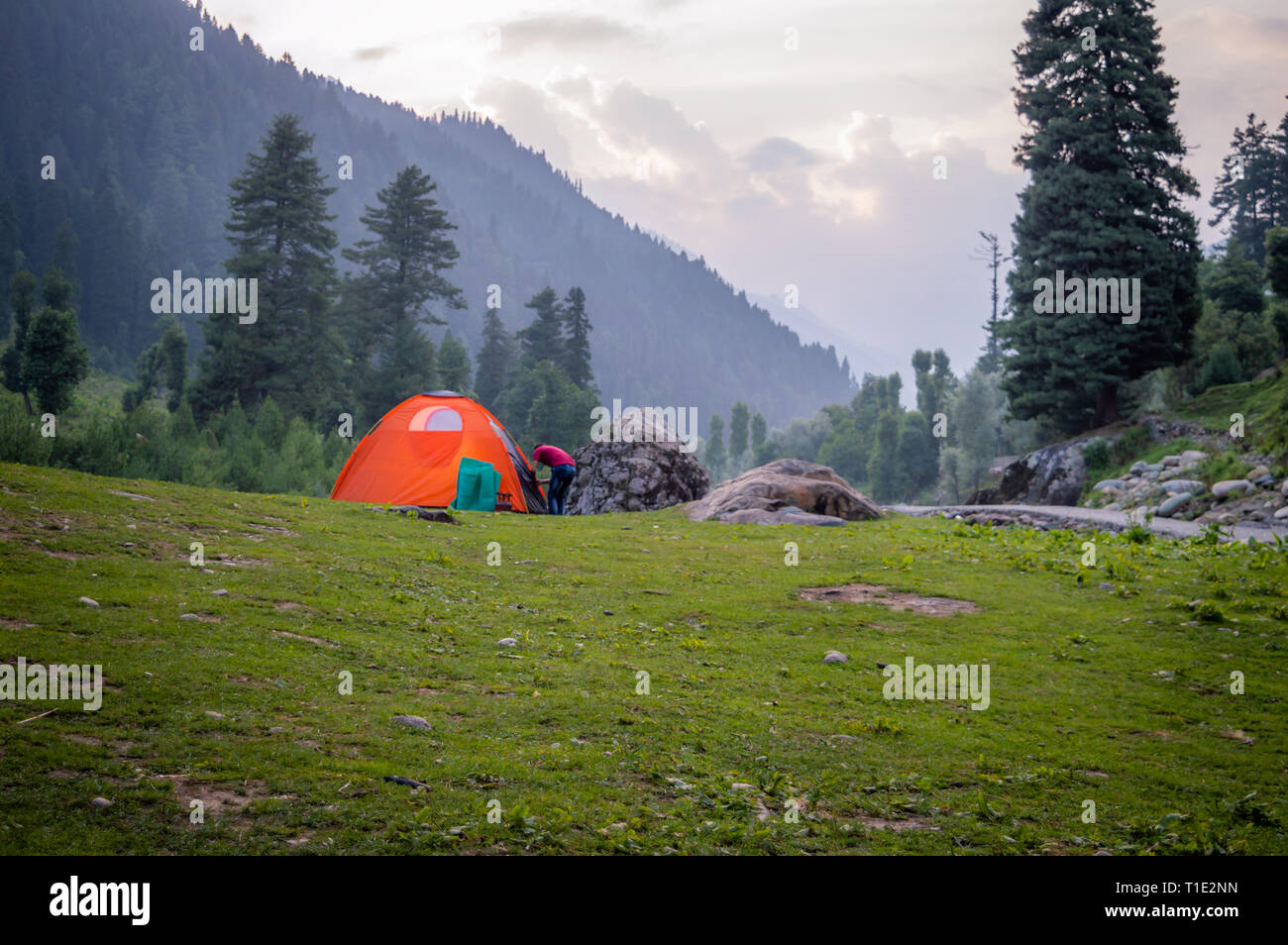 A person entering an Orange coloured tent set up for camping in the Himalayan region of Kashmir - Stock Image