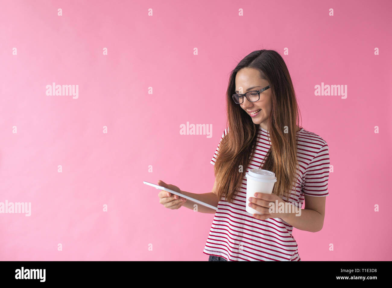 A beautiful girl uses a tablet and drinks coffee or another drink. Communication or job search online or internet entertainment during coffee break. - Stock Image
