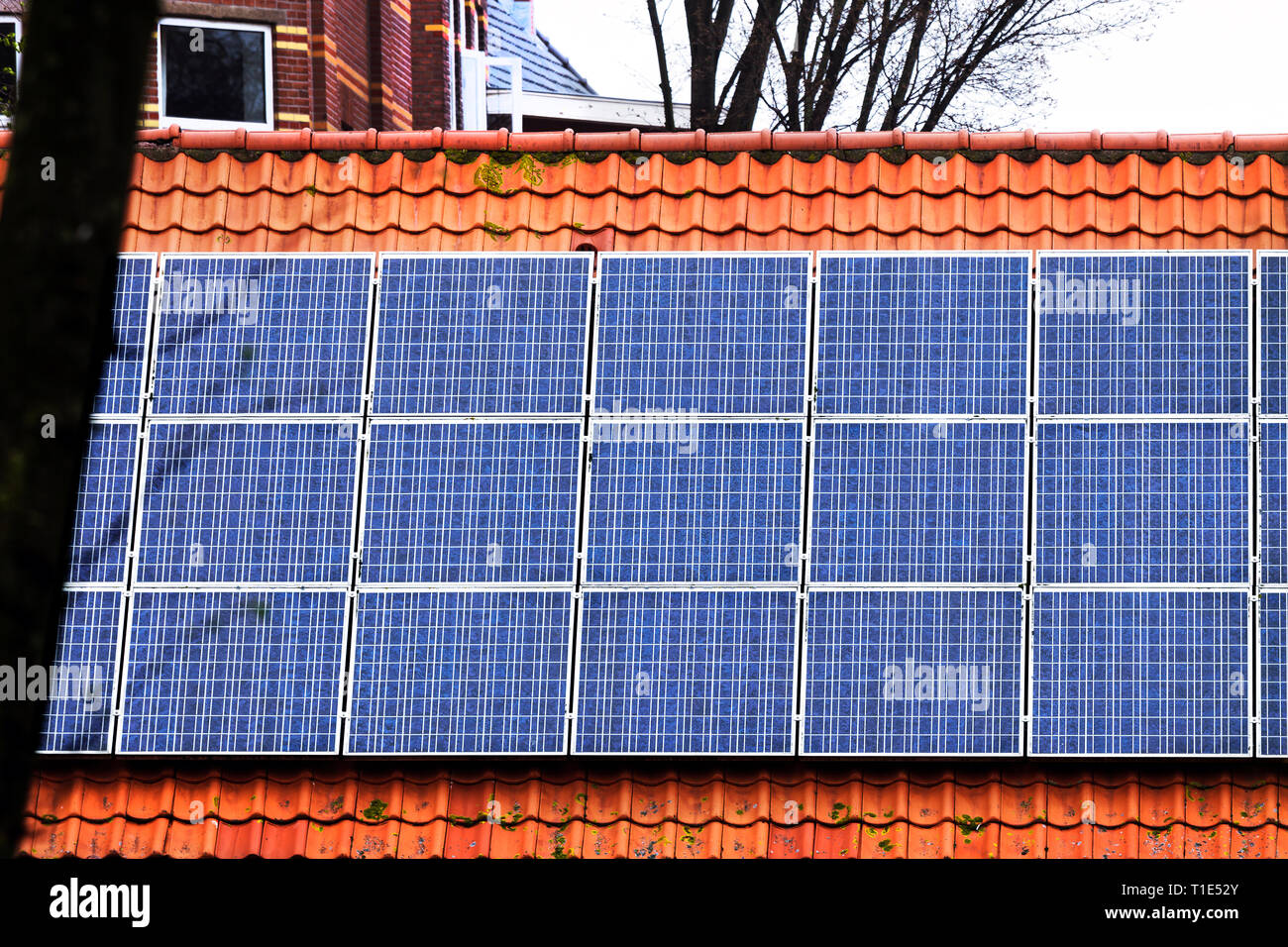 Red tile Roof with solar panels. New solar technologies on the old house. - Stock Image
