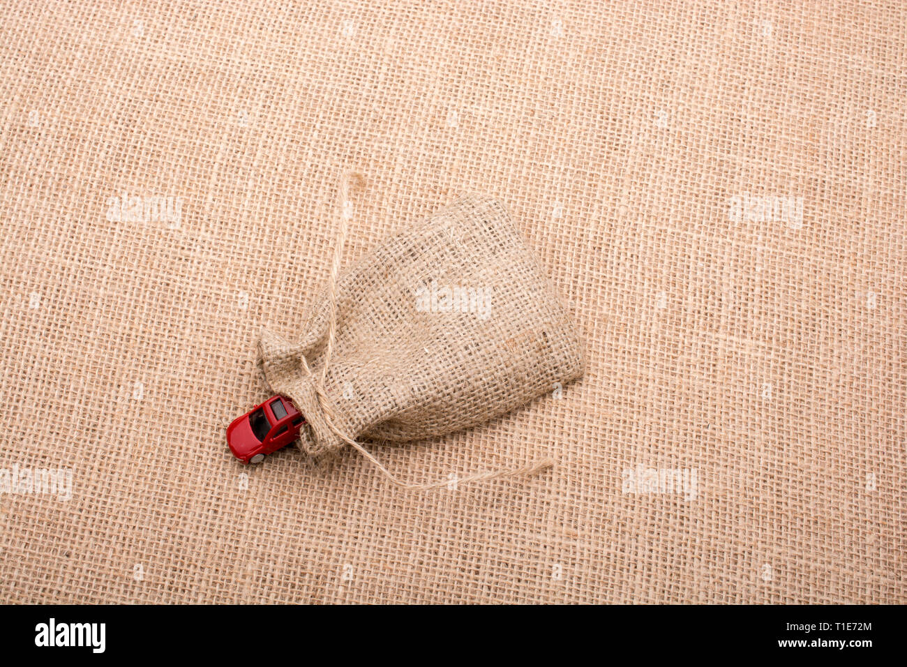 Red toy car coming out of a linen sack on a linen canvas - Stock Image