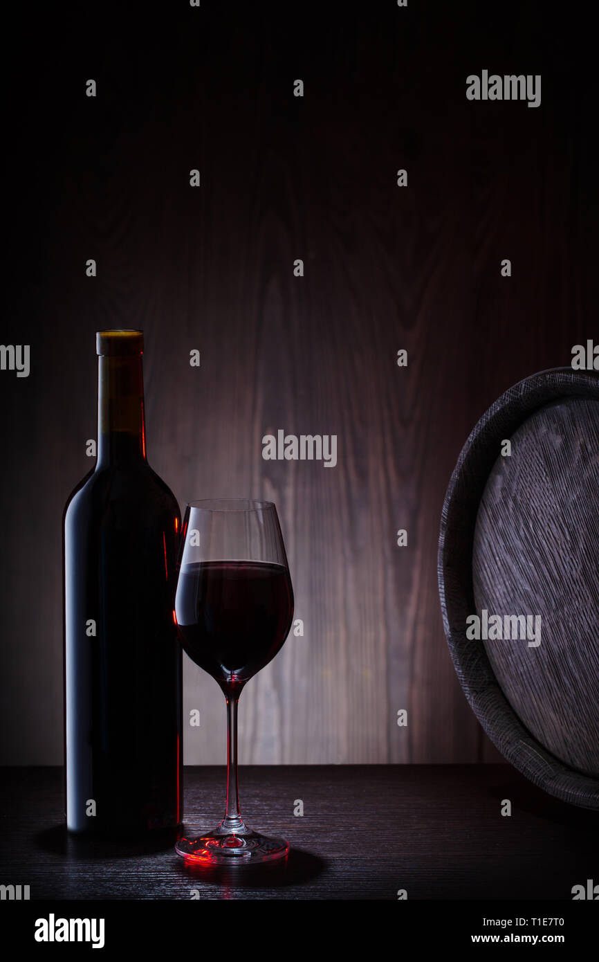 Red wine in glass and bottle on background of barrels and planks - Stock Image