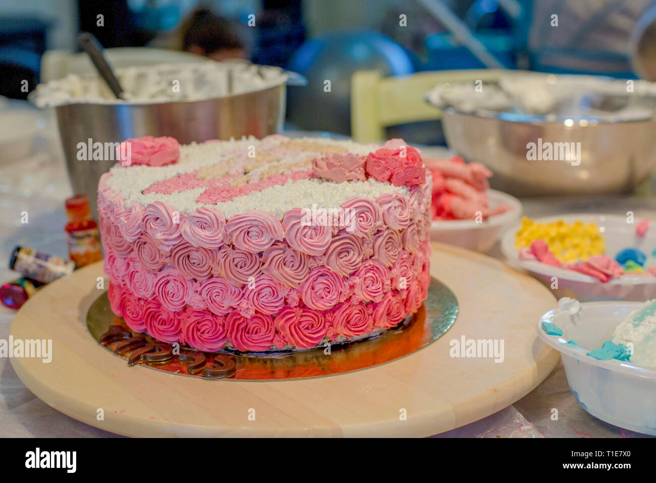 Decorating a birthday cake with icing sugar unicorn - Stock Image