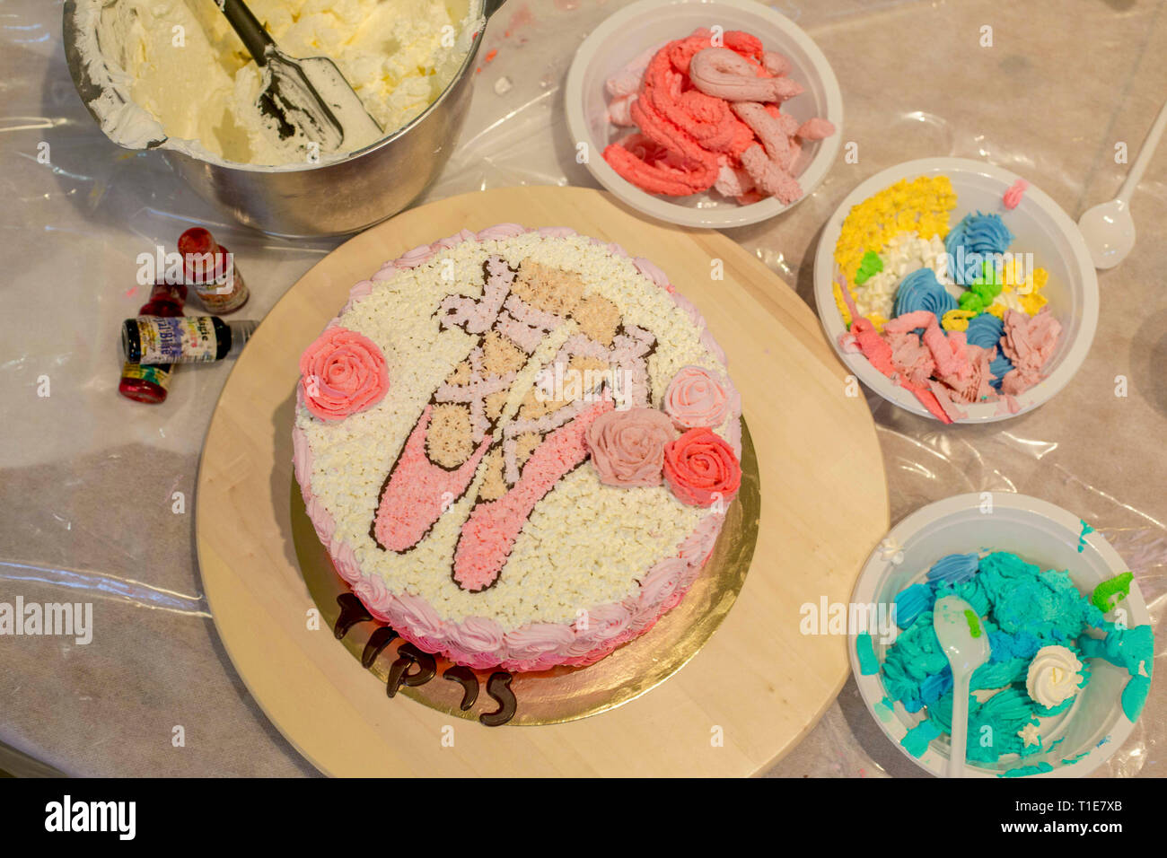 Decorating a birthday cake with icing sugar ballet shoes, - Stock Image