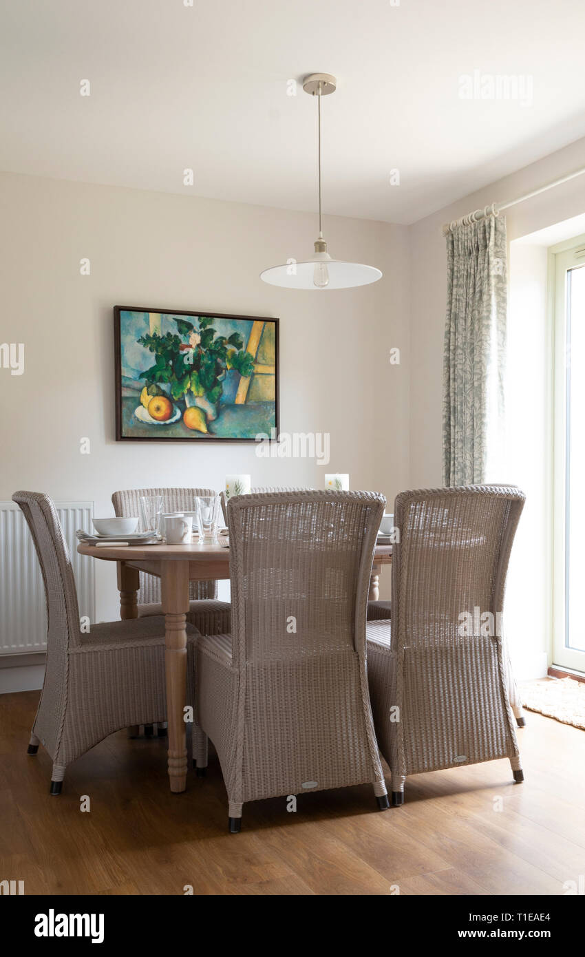 Dining table, set with fruit artwork on the wall - Stock Image