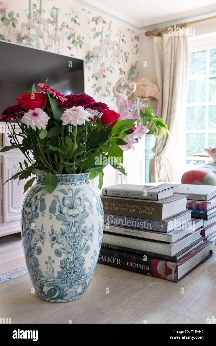Tight crop of living room's coffee table featuring a vase of flowers - Stock Image
