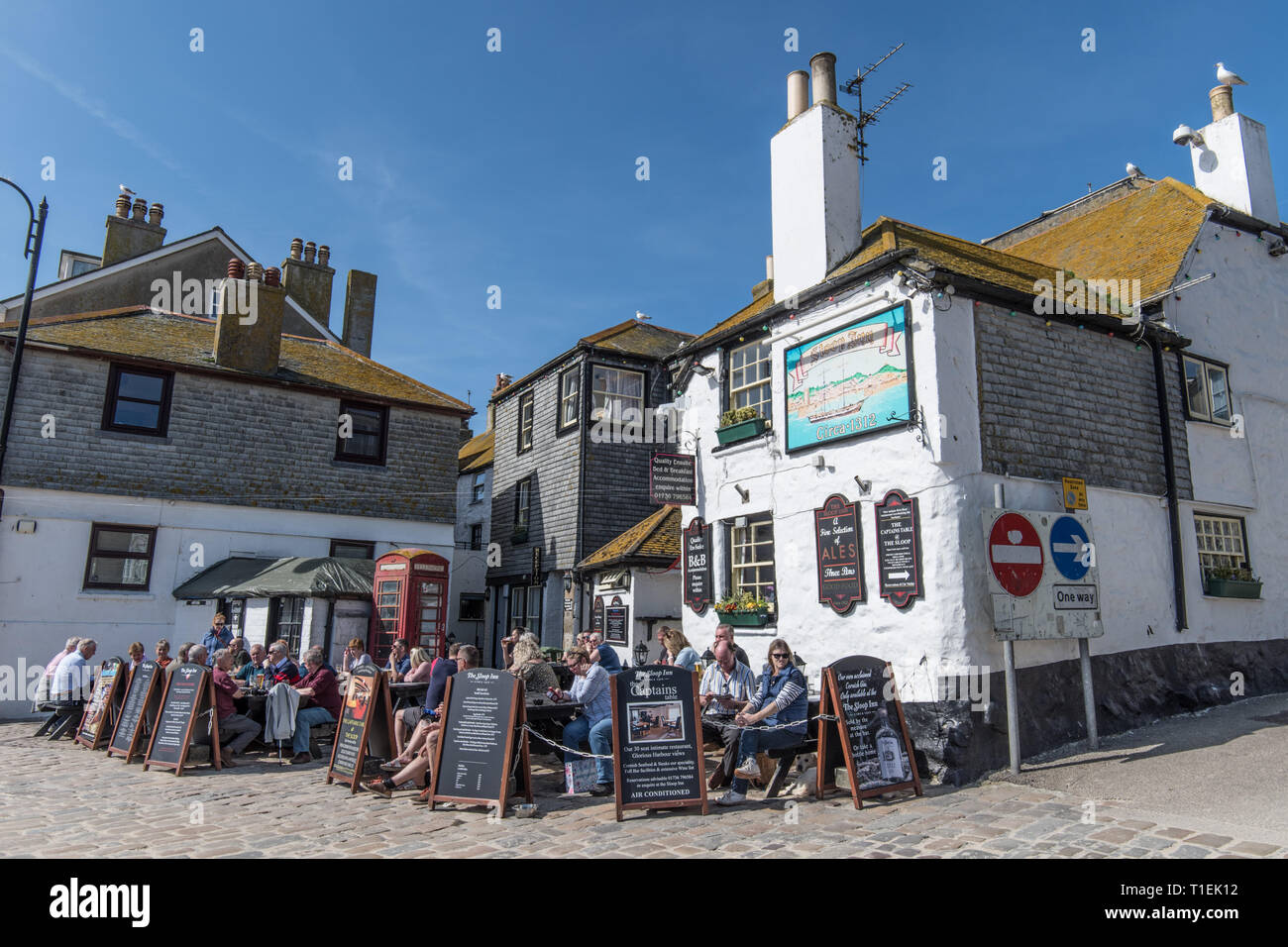 St Ives, Cornwall, UK. 26th Mar, 2019. UK Weather. It was a hot and sunny afternoon on the coast at St Ives in Cornwall today. People were making the most of the weather having a pint outside the famous Sloop Inn. Credit: Simon Maycock/Alamy Live News - Stock Image