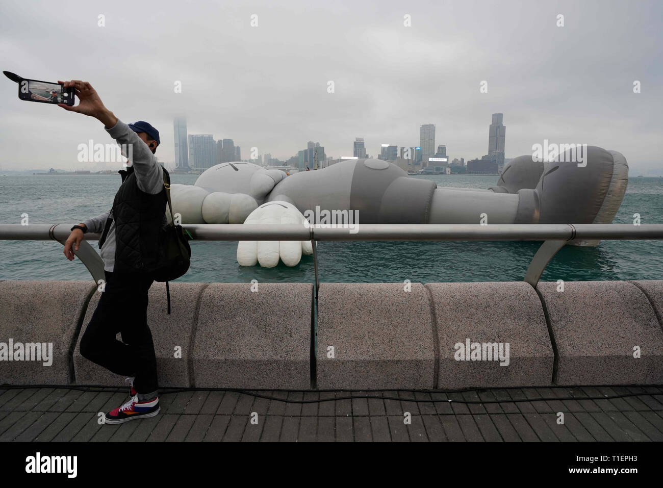 Hong Kong, China. 26th Mar, 2019. A visitor takes a photo of himself with the KAWS:HOLIDAY installation on display in Hong Kong's Victoria Harbor. The KAWS:Holiday enlarged structure by American artist Brian Donnelly, also known as KAWS, will be on display until March 31, 2019. Credit: Christopher Jue/ZUMA Wire/Alamy Live News Stock Photo
