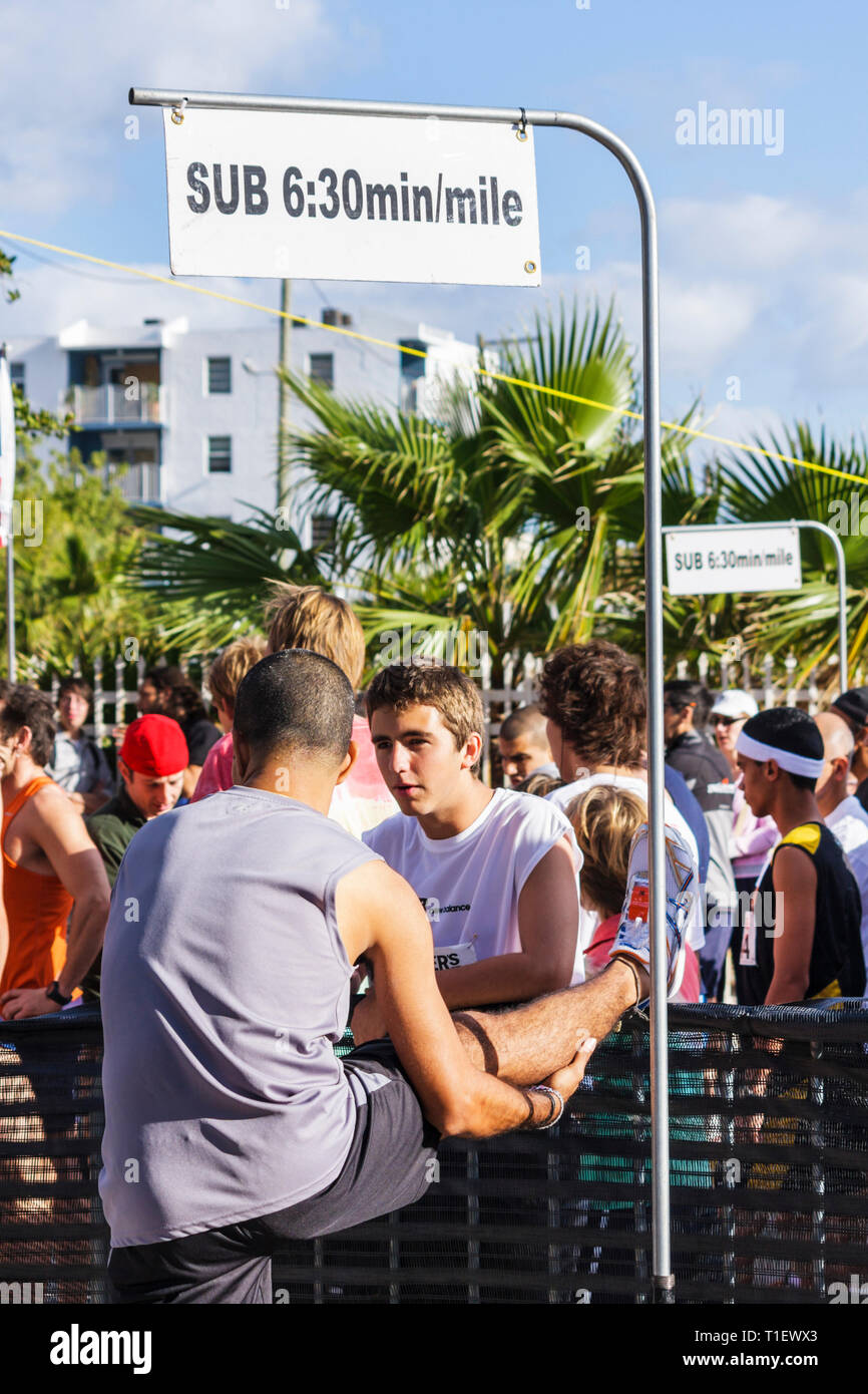 Miami Beach Florida Ocean Drive South Pointe 5K Run benefit runners race compete starting line Hispanic man boy teen stretchin - Stock Image