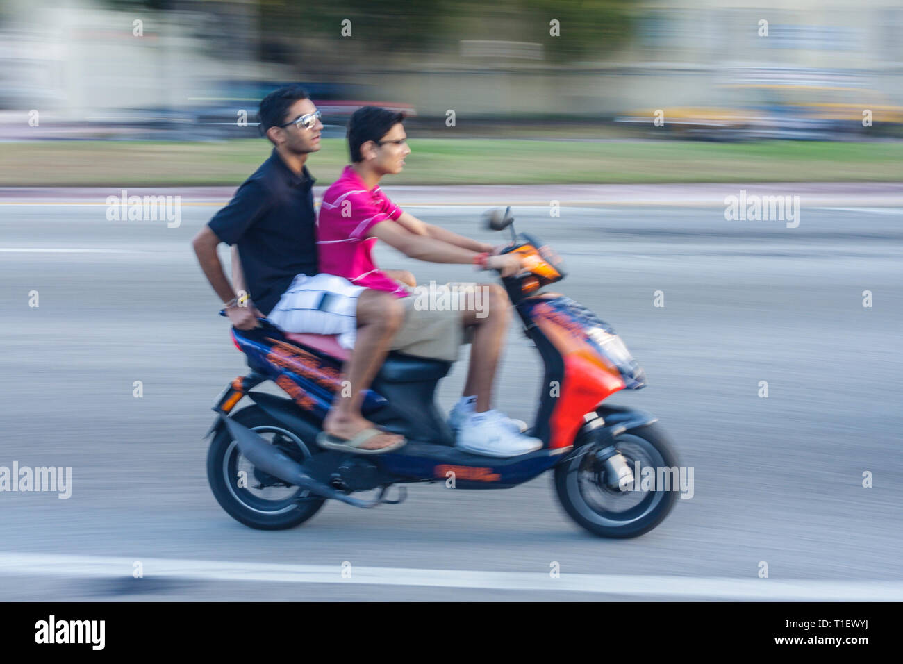 Miami Beach Florida Washington Avenue Asian man men motor scooter moving speed no helmet unsafe transportation two wheels rent - Stock Image