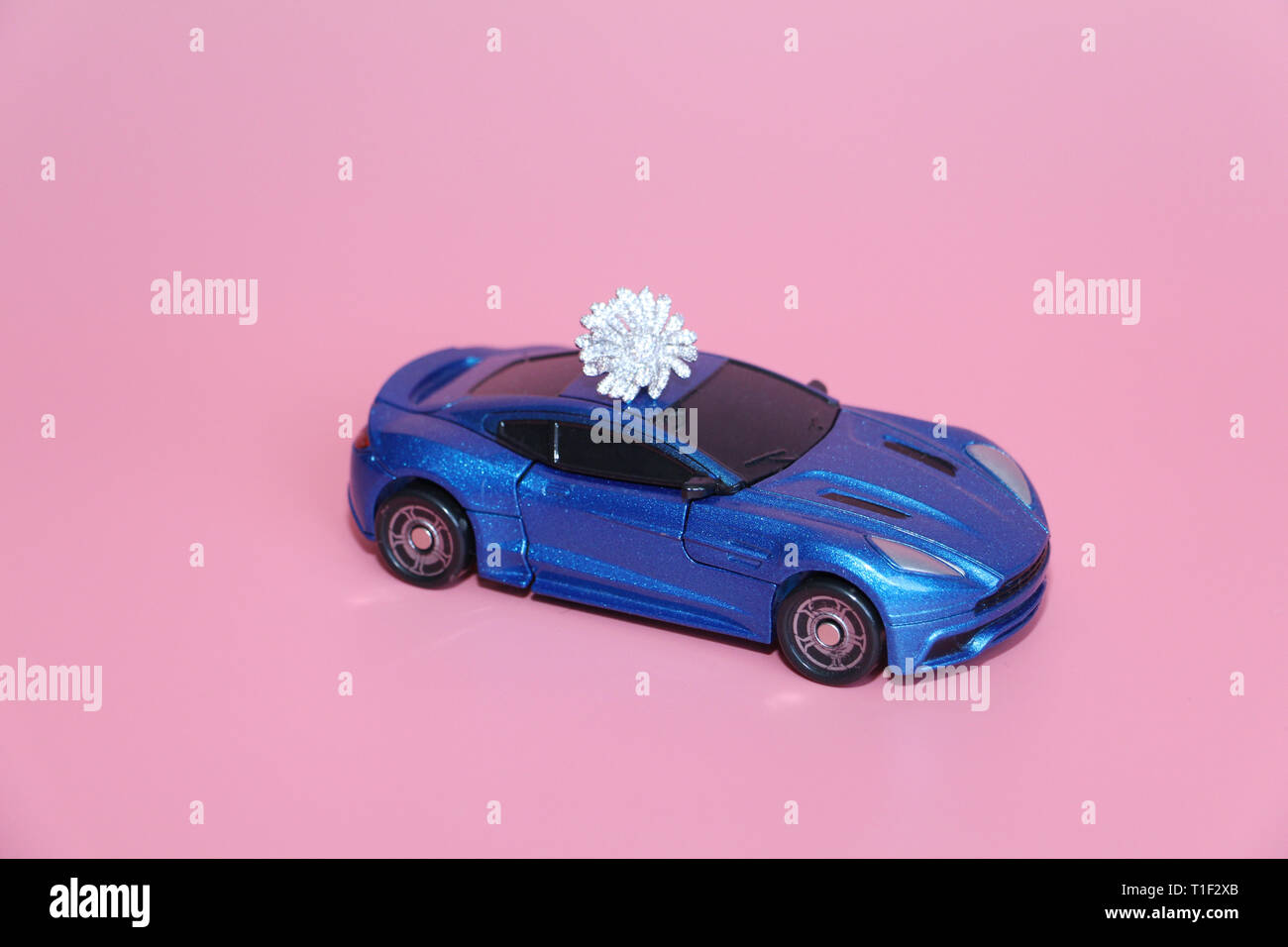 The blue sports car carries a crystal flower. The gift lies on the roof of the car. Pink background. Toy for children. There are no people. Stock Photo