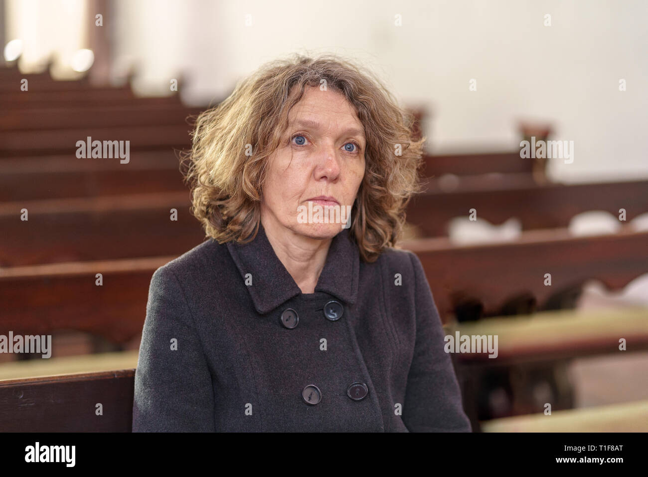 Religious woman sitting alone in a church pew looking ahead towards the altar deep in spiritual thought and praying - Stock Image