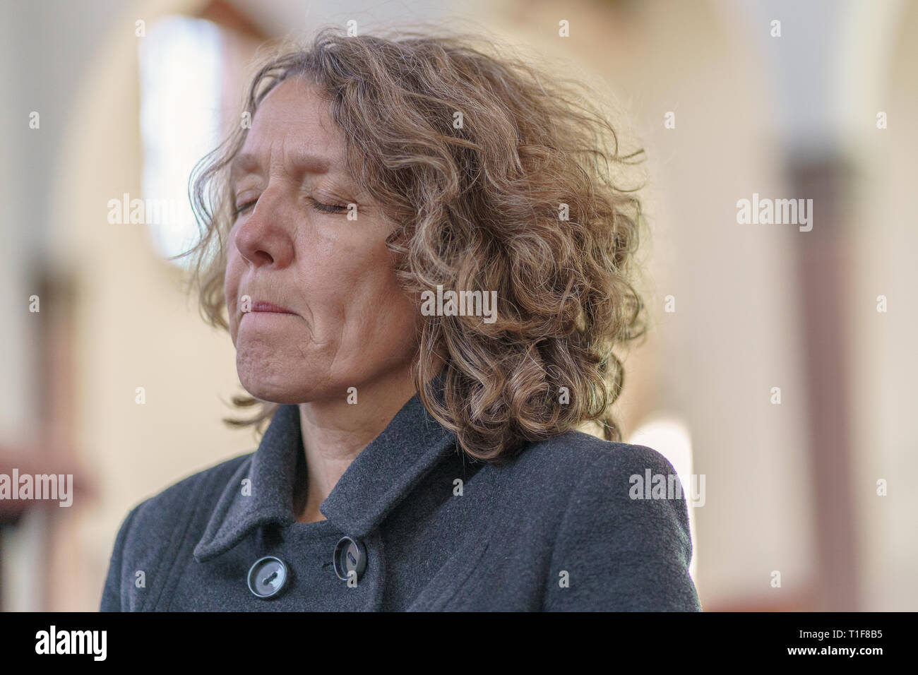 Religious devout woman praying alone in a church with her eyes closed in concentration in a close up portrait - Stock Image