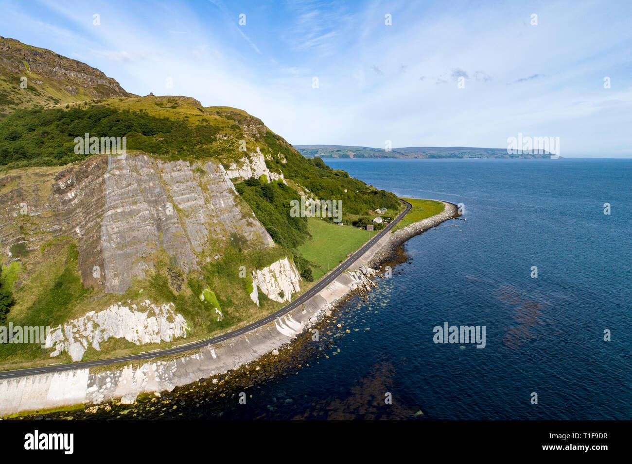 Northern Ireland, UK. Atlantic coast. Cliffs and A2 Antrim Coast Road, a.k.a. Giants Causeway Coastal Route. One of the most scenic coastal roads in E - Stock Image