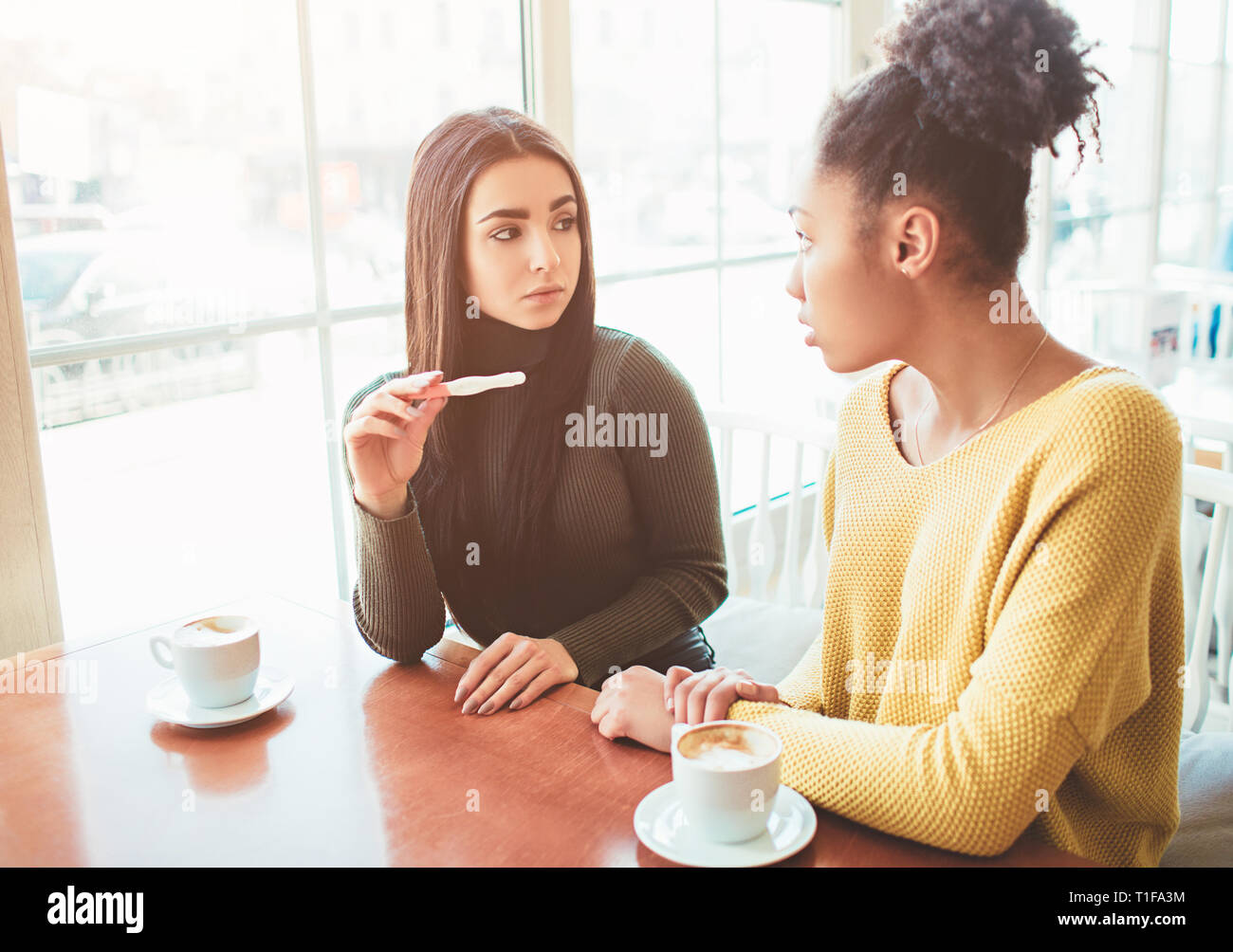 Sad picture of girls sitting. One of them is holding a pregnancy test that shows she will soon become a young mother but girl is not happy about that - Stock Image