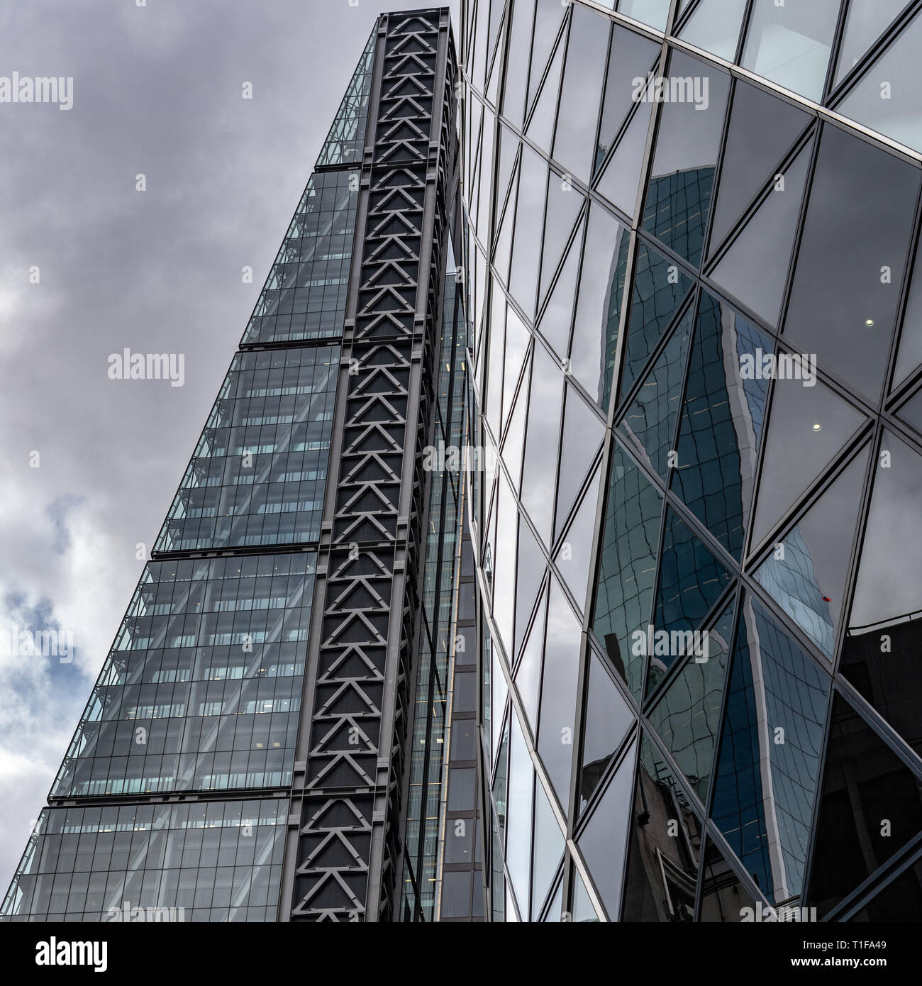 The curves of the 'Gherkin' contrast with the angular style of the 'Cheesegrater' in the City of London. - Stock Image