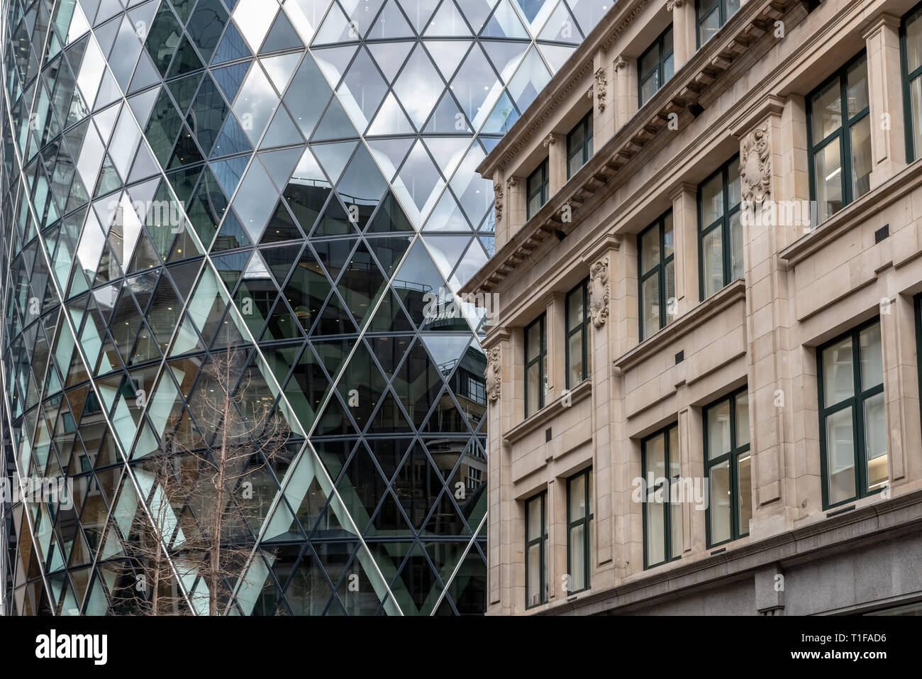 The curved glass and steel of the 'Gherkin' contrast with the more classical design of the buildings in Bury St, City of London - Stock Image