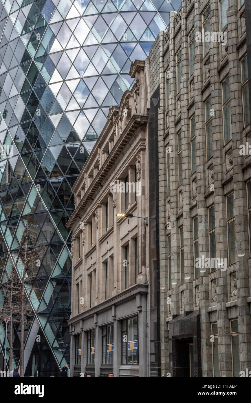 The curved glass and steel of the 'Gherkin' contrast with the classical and art deco buildings in Bury St, City of London - Stock Image