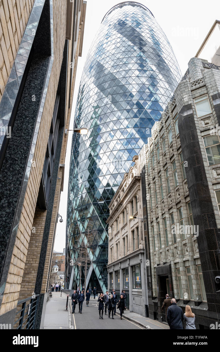 The 'Gherkin' (30 St Mary Axe) towers over Holland House and the more traditional buildings of Bury Street in the City of London - Stock Image
