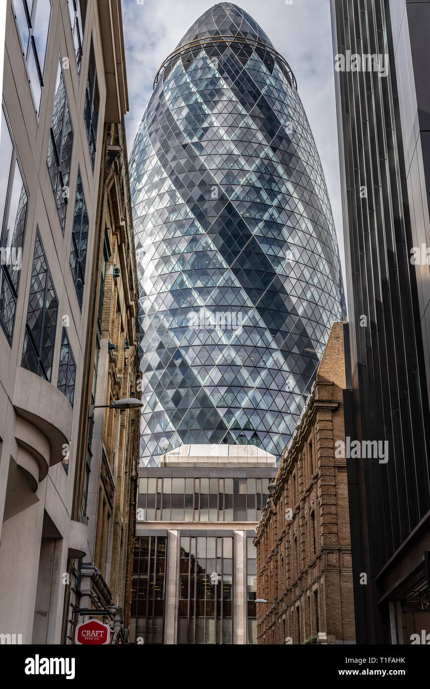 The 'Gherkin' (30 St Mary Axe) towers over the more traditional buildings of Mitre Street in the City of London - Stock Image