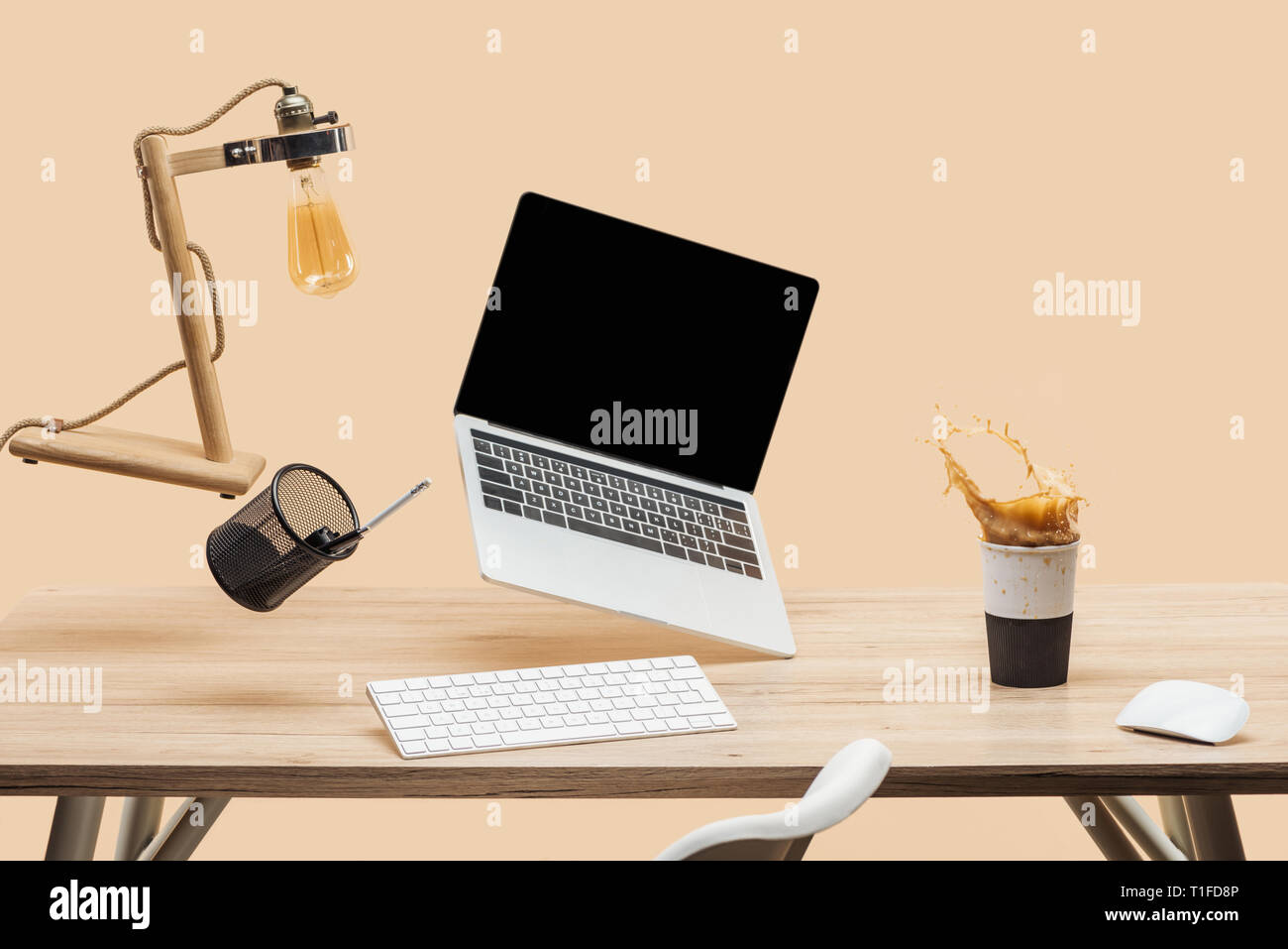 laptop with blank screen and lamp levitating in air above workplace with thermomug with coffee splash isolated on beige Stock Photo