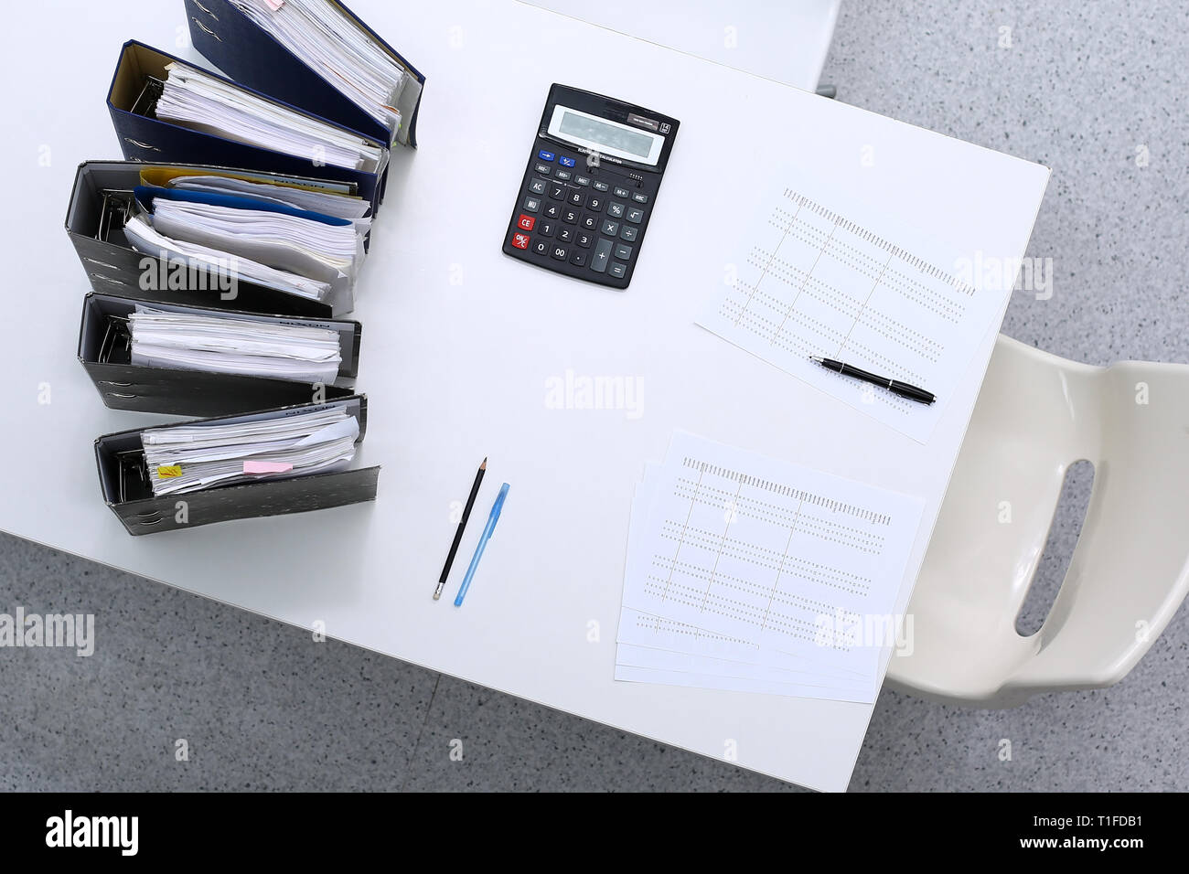 Binders with papers are waiting to be processed with bookkeeper. Internal Revenue Service inspector working place. View from above - Stock Image