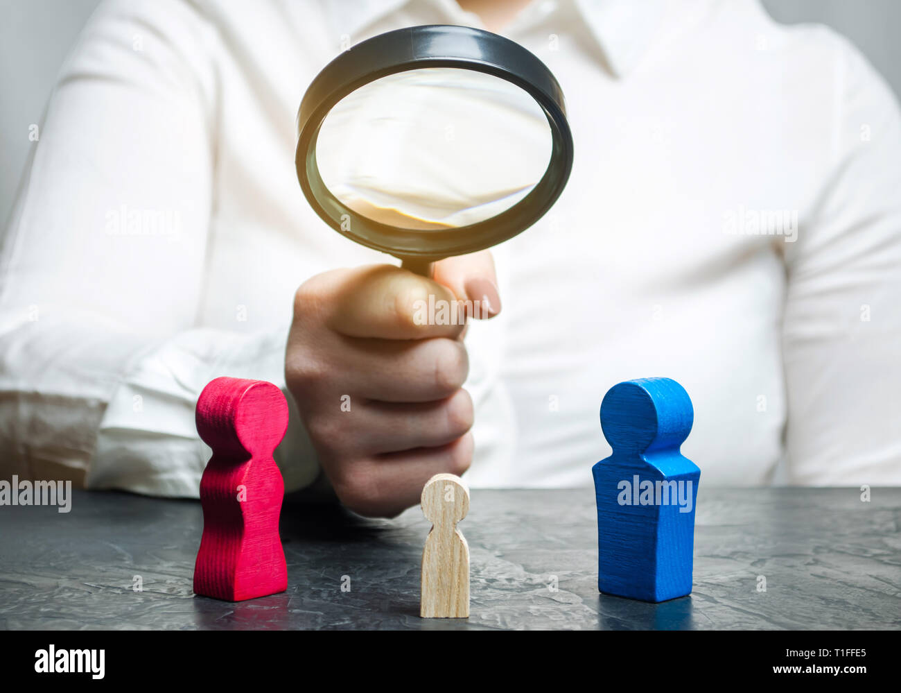 The doctor's hand is holding a magnifying glass over the child's figure. The court decision on custody of the child by one of the parents after the di - Stock Image