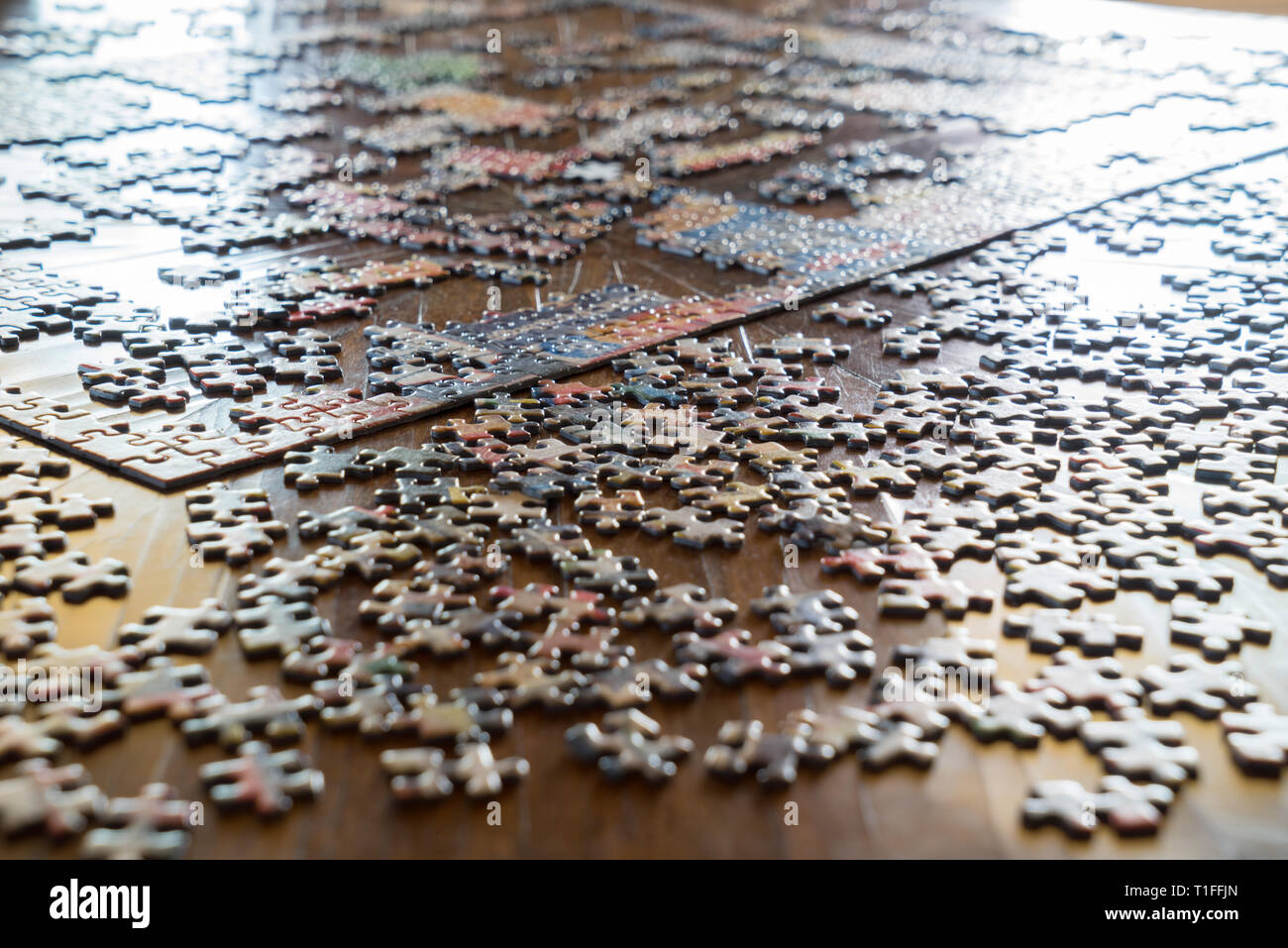 Incomplete Jigsaw puzzle, pieces on table - Stock Image