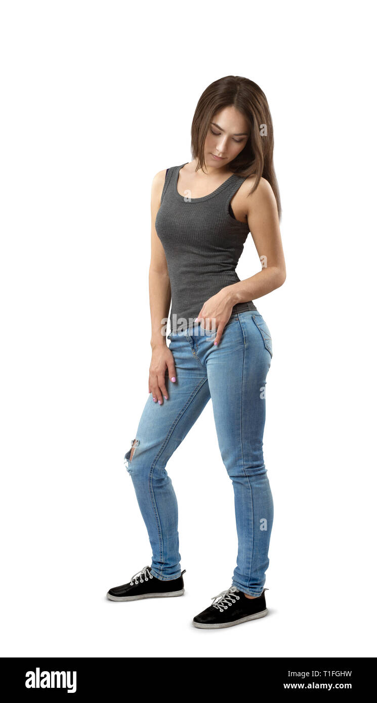 Young woman in sleeveless top and jeans standing in half-turn looking down isolated on white background. - Stock Image