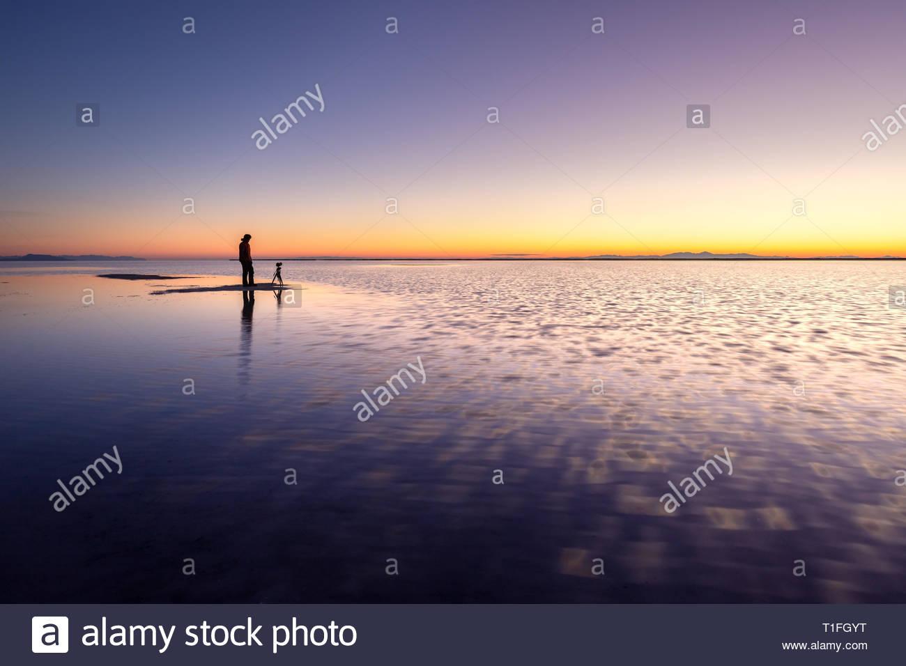 Photographer standing on the shallow water at dawn, Bonneville Salt Flats near Great Salt Lake, Utah Stock Photo