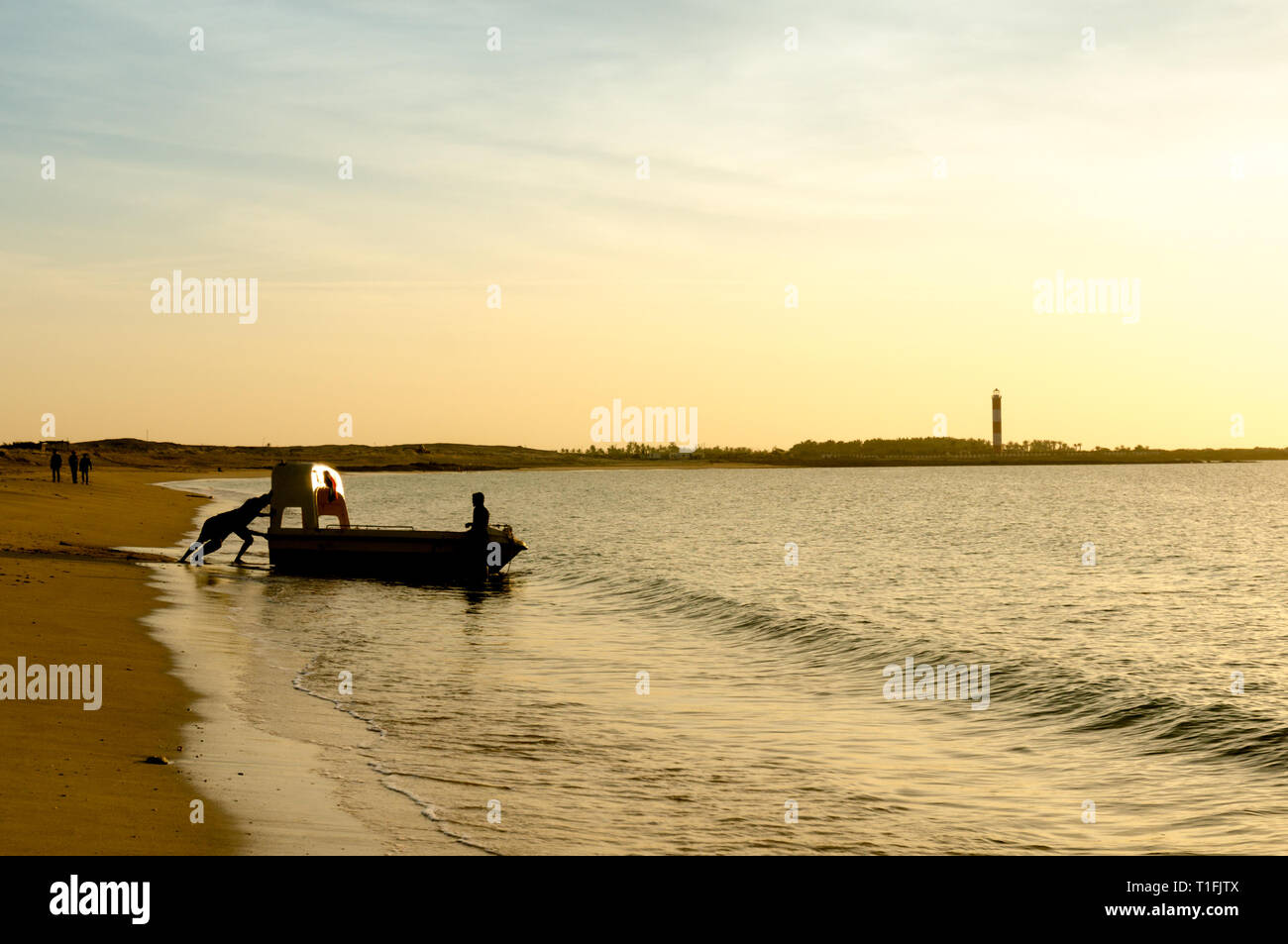 Silhouette of men pulling a boat into the sea at a beach in Gujarat Stock Photo