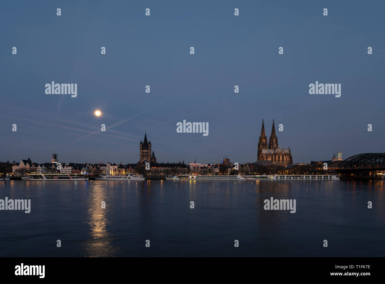 Köln, Blick von der rechten Rheinseite auf Dom, Groß-Sankt-Martin und Rathaus kurz vor Sonnenaufgang bei Vollmond - Stock Image