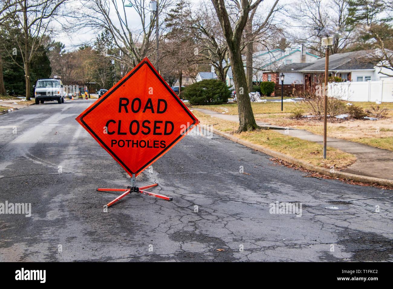 Orange triangular road sign on a small suburban street that says Road Closed Potholes - Stock Image