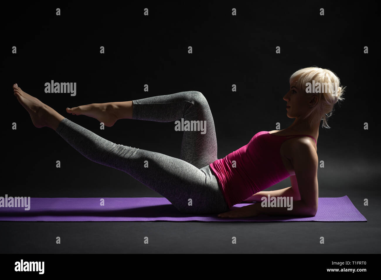 Woman exercising pilates. Half seated leg lift exercise. - Stock Image