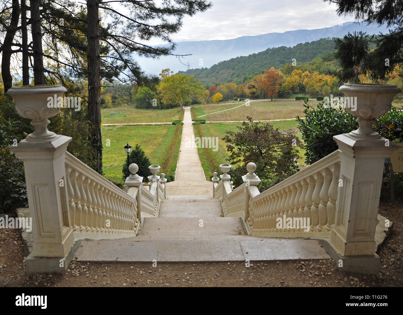 A white stone staircase in the autumn garden leads to the yellow autumn trees on a background of mountains with autumn clouds Stock Photo