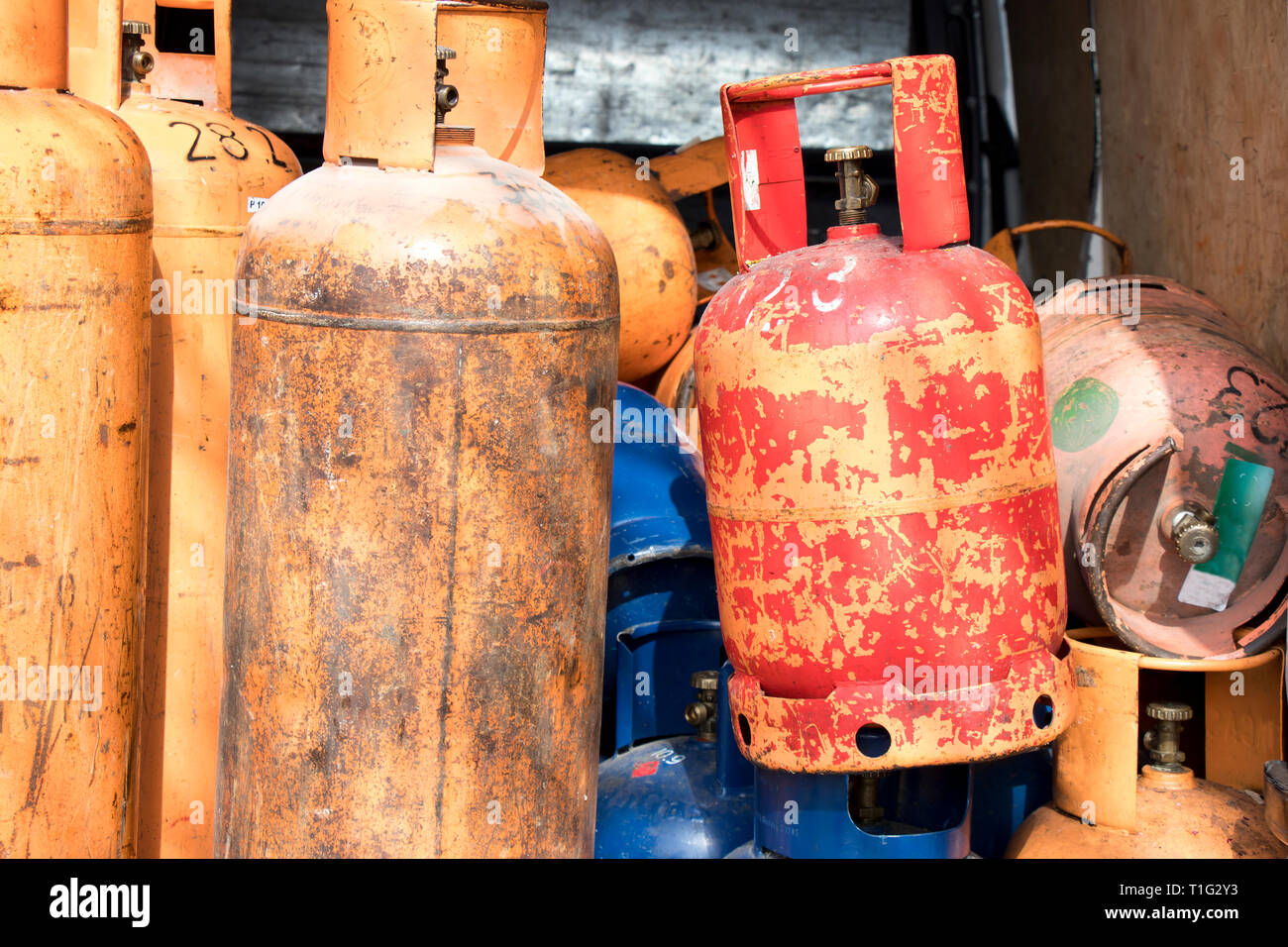 Different color and size cylinder gas bottles stored for refill and supply - Stock Image