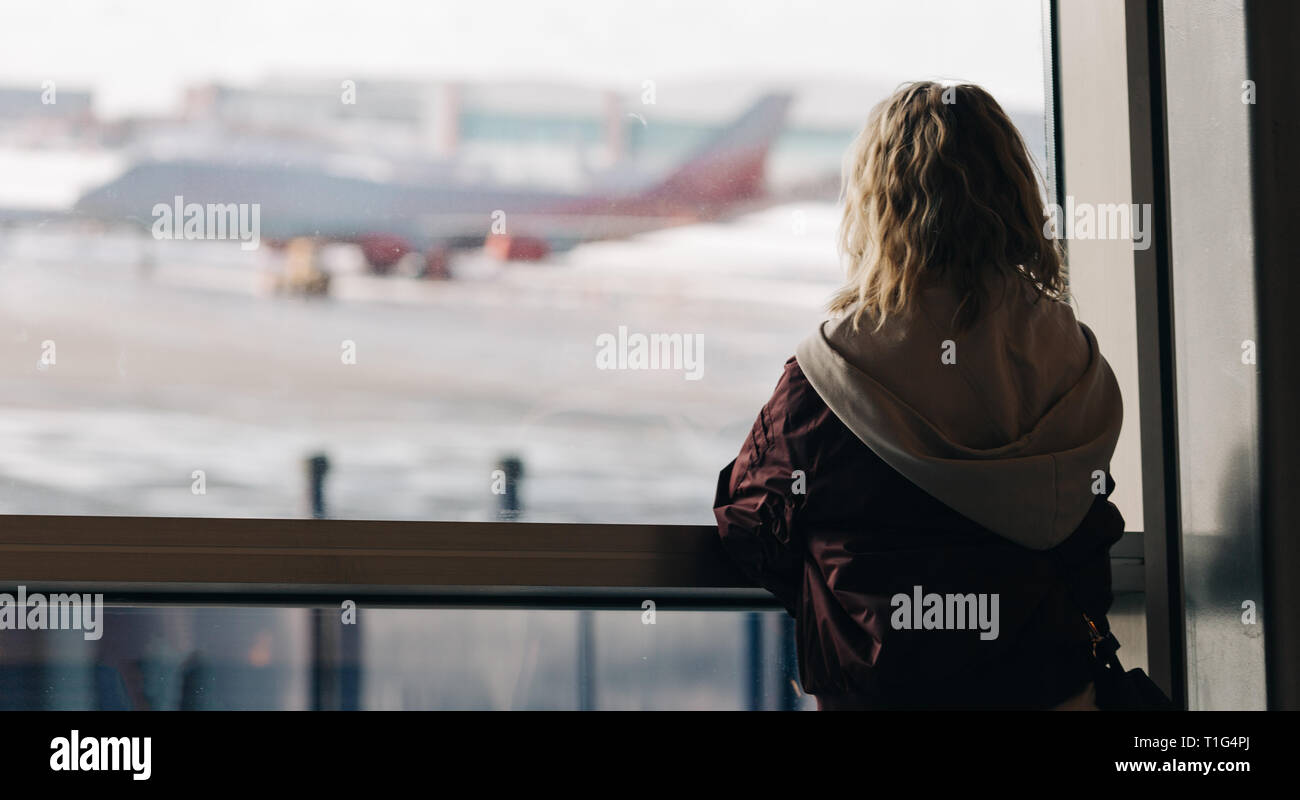 Photo from back of blonde near window with plane flying by in afternoon . Stock Photo