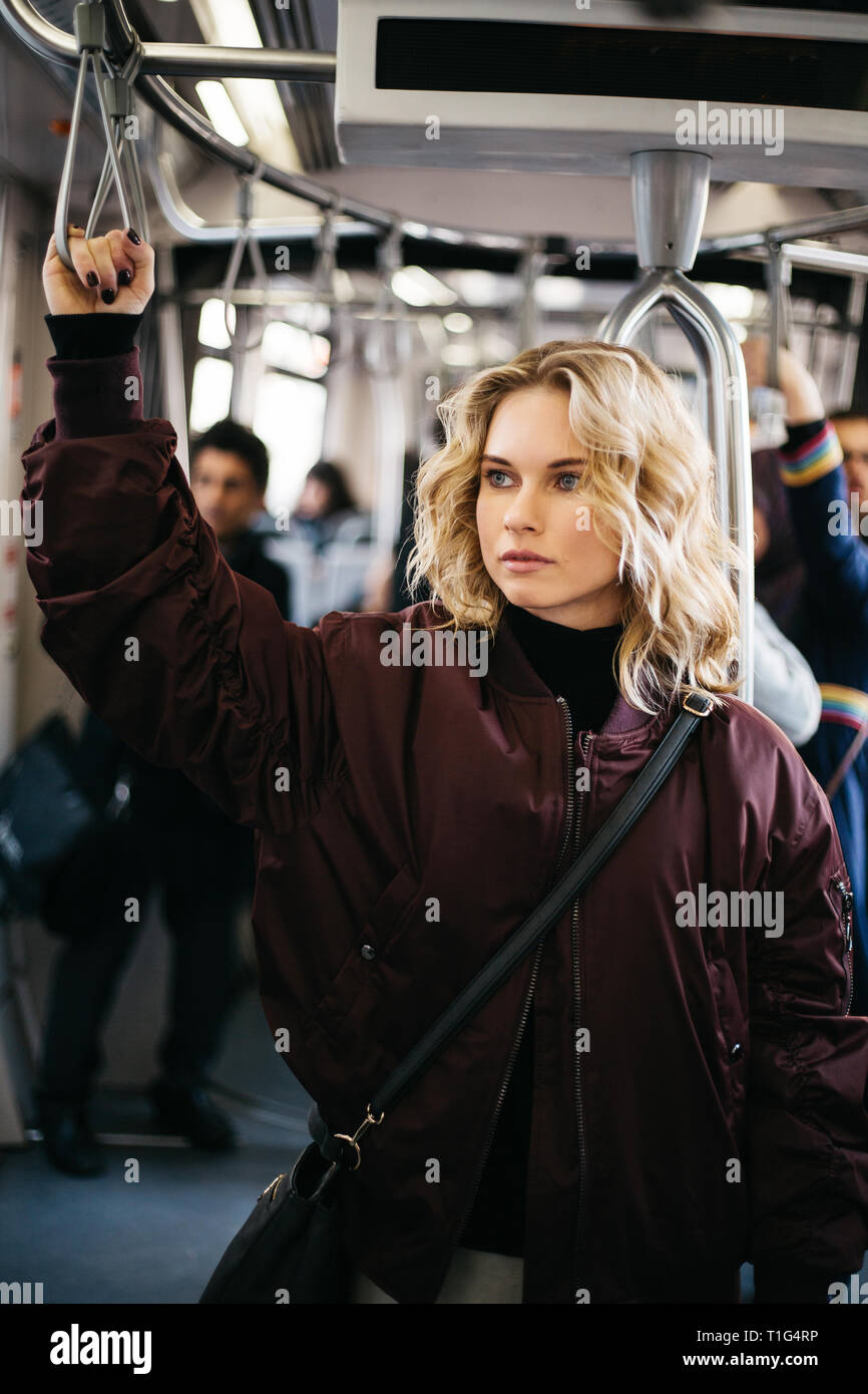 Photo of curly blonde woman riding in bus. Stock Photo