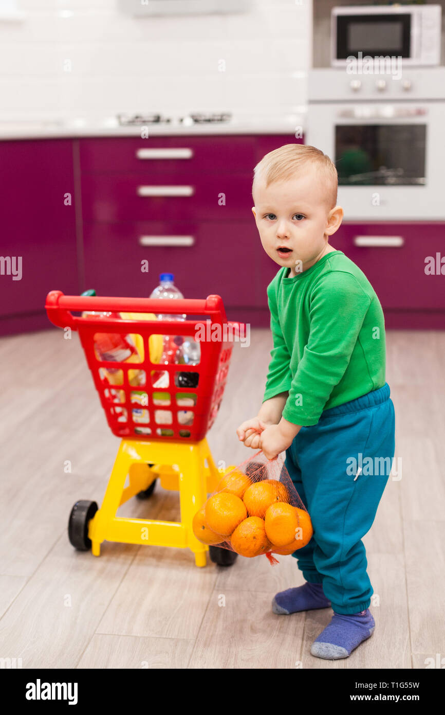 Little boy holds a grid with oranges. Little kid in casual wear carrying child plastic shopping trolley. Shopping, discount, sale concept Stock Photo