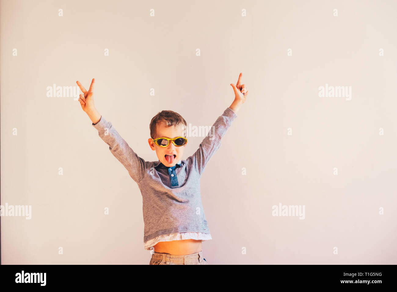 Child with funny sunglasses raising arms excited in victory sign. - Stock Image