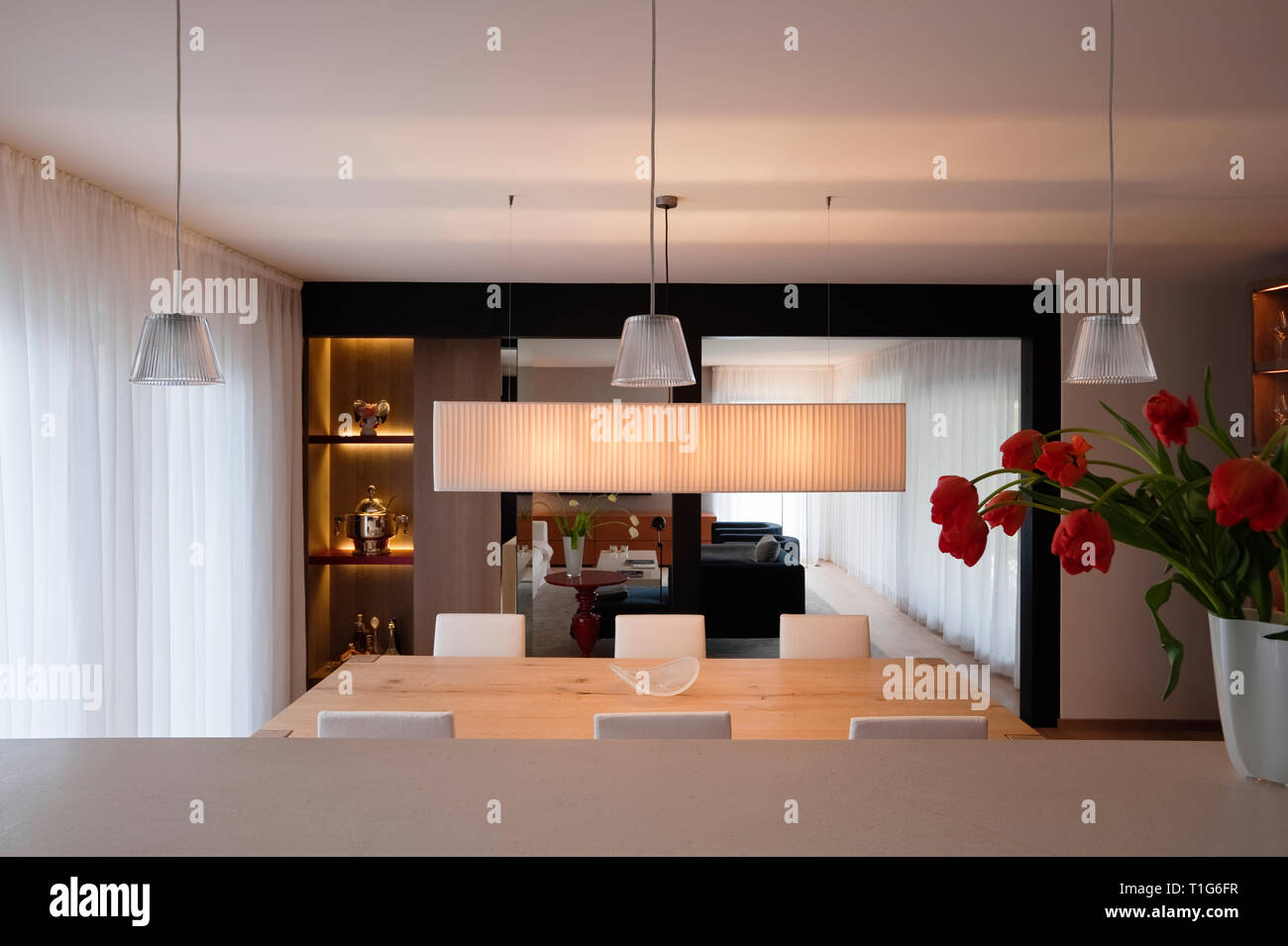 Modern dining room with white pendant lights - Stock Image