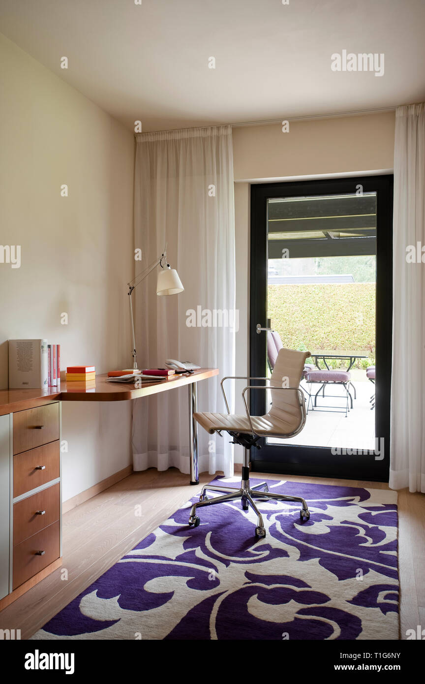 Modern office with purple patterned rug - Stock Image