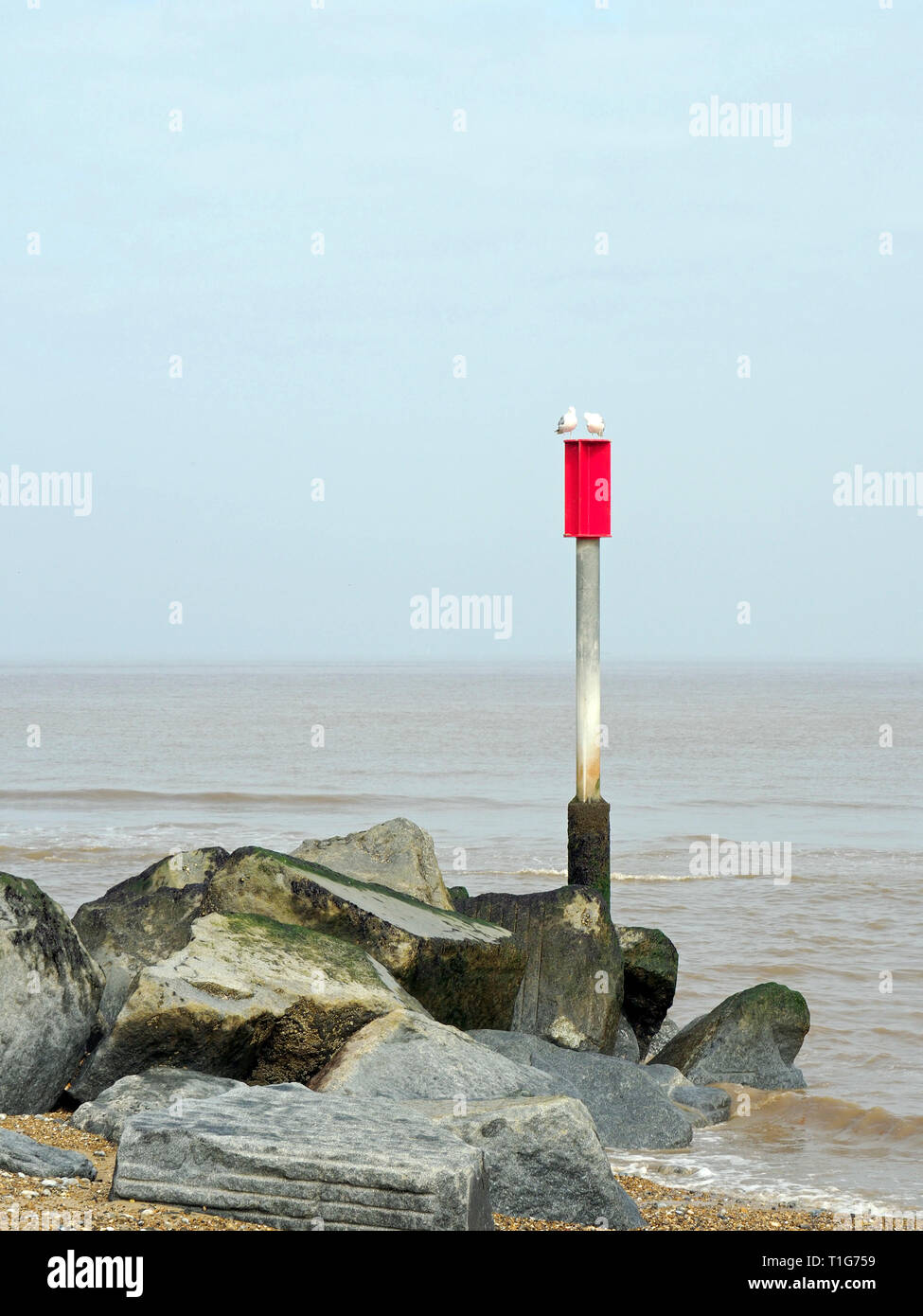 A rock groyne on Horsey Beach, Norfolk traps sand from the longshore drift.The pylon and red warning plate are for the protection in inshore boats. Stock Photo