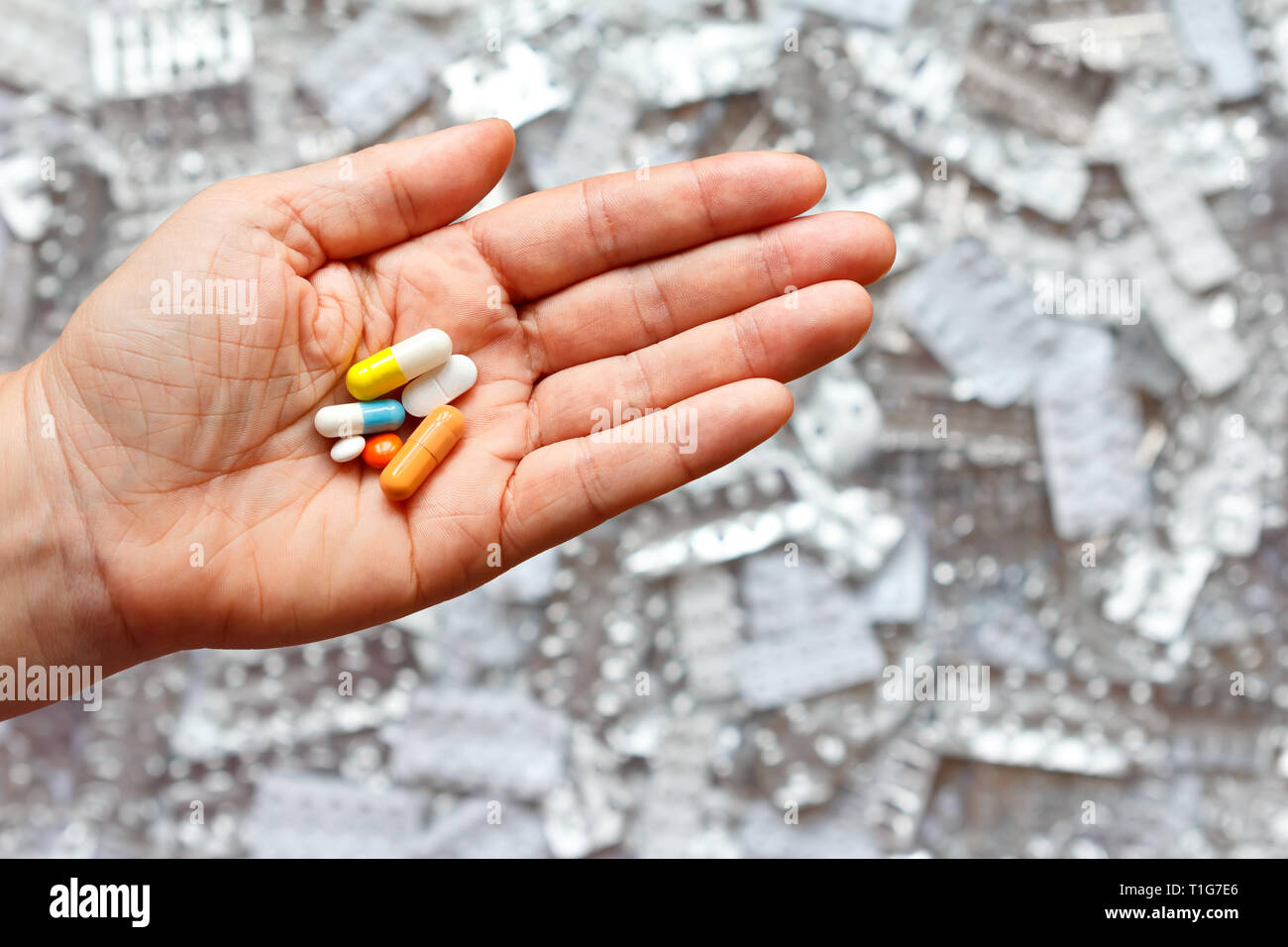 Hand with many different tablets in front of empty blister packages, multi-medication concept Stock Photo