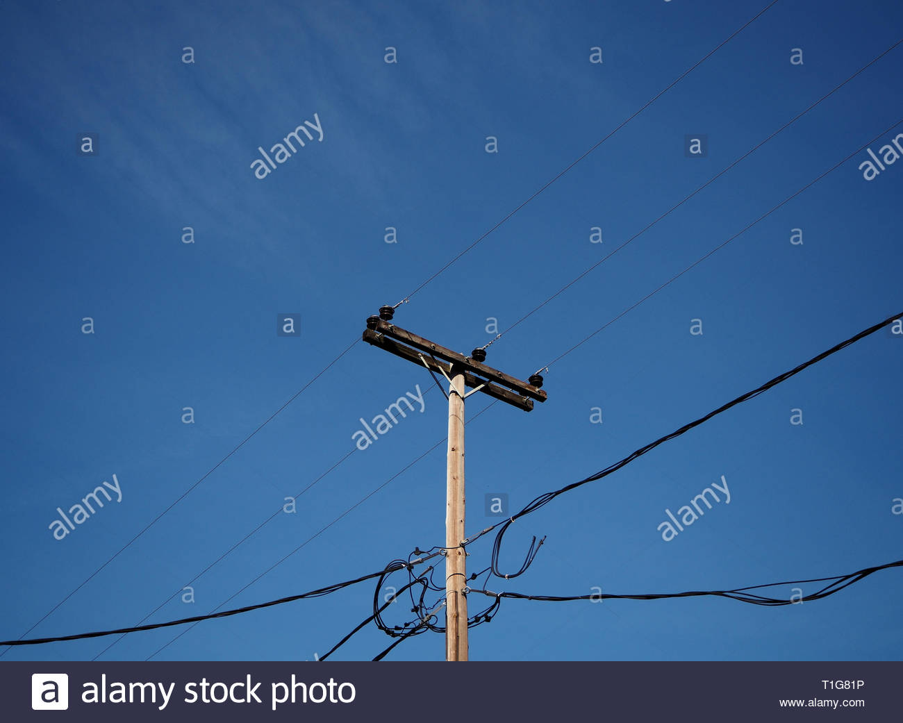 A grids view ,electric current pylon and cables isolated against blue sky - Stock Image